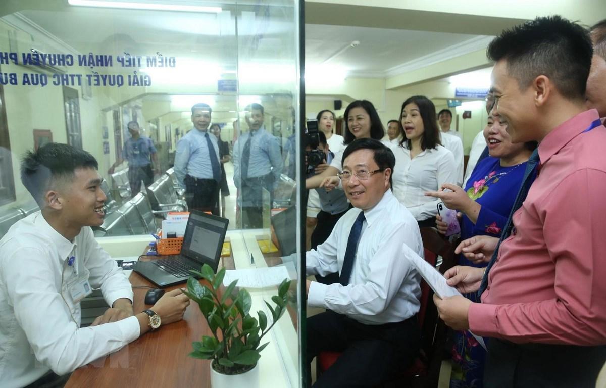 Phó Thủ tướng, Bộ trưởng Bộ Ngoại giao Phạm Bình Minh kiểm tra, thử nghiệm các hoạt động của Bộ phận tiếp nhận hồ sơ và trả kết quả giải quyết thủ tục hành chính một cửa thuộc Cục Lãnh sự. (Ảnh: Lâm Khánh - TTXVN)
