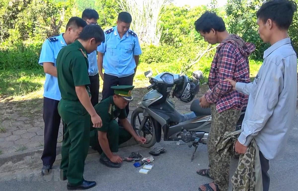 Lực lượng chức năng kiểm tra xe máy của đối tượng Lò Văn Sáng (áo ca rô). (Ảnh: TTXVN phát)
