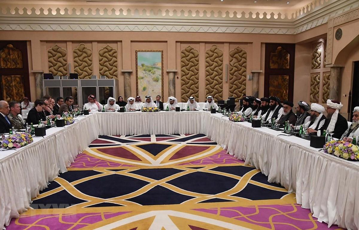 Phái đoàn Mỹ (trái) và phái đoàn Taliban (phải) tại vòng đàm phán hòa bình ở Doha, Qatar ngày 26/2. (Ảnh: AFP/TTXVN)