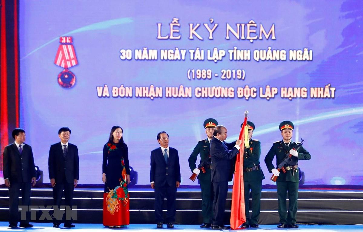 Thủ tướng Nguyễn Xuân Phúc gắn Huân chương Độc lập hạng Nhất lên cờ truyền thống của tỉnh Quảng Ngãi. (Ảnh: Thống Nhất/TTXVN)