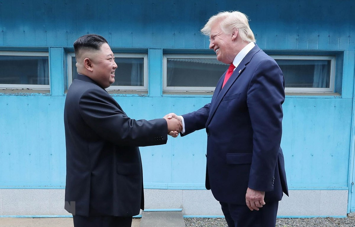Tổng thống Mỹ Donald Trump (phải) và nhà lãnh đạo Triều Tiên Kim Jong-un (trái) bất ngờ gặp lại nhau tại DMZ. (Ảnh: AFP/TTXVN)
