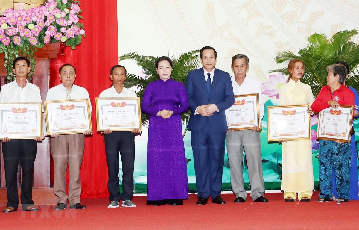 Chủ tịch Quốc hội Nguyễn Thị Kim Ngân và Bộ trưởng Bộ Lao động Thương binh xã hội Đào Ngọc Dung trao Bằng Tổ quốc ghi công cho thân nhân các gia đình. (Ảnh: Trọng Đức/TTXVN)