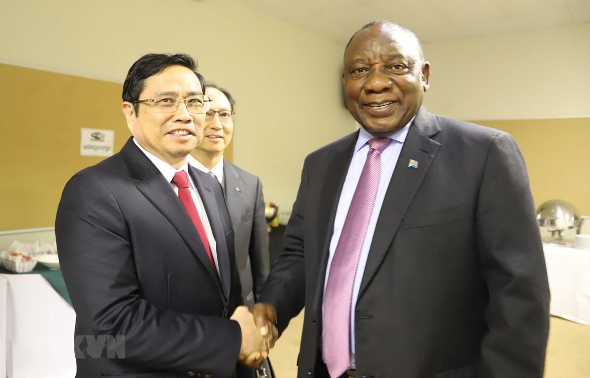 Chủ tịch Đảng Đại hội Dân tộc Phi (ANC) Cyril Ramaphosa đón chào đồng chí Phạm Minh Chính tại thủ đô Pretoria. (Ảnh: Phi Hùng/TTXVN)