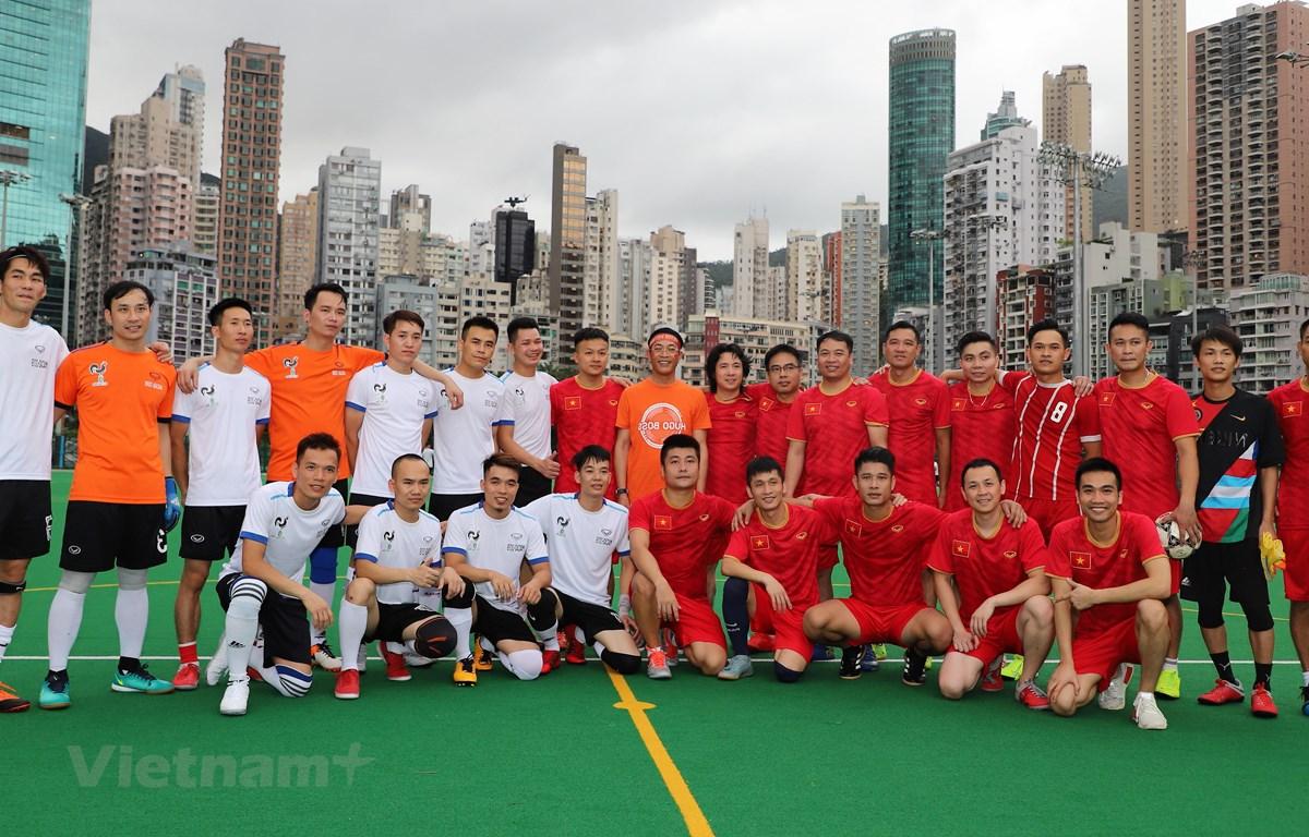 Tổng Lãnh sự Trần Thanh Huân (áo vàng đứng giữa) chụp ảnh lưu niệm với các cầu thủ.  (Ảnh: PV/Vietnam+)