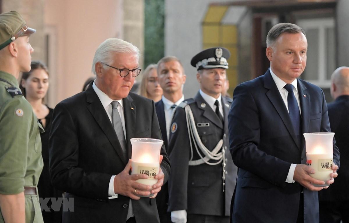 Tổng thống Đức Frank-Walter Steinmeier (trái) và Tổng thống Ba Lan Andrzej Duda (phải) thắp nến tưởng nhớ các nạn nhân. (Ảnh: PAP/TTXVN)