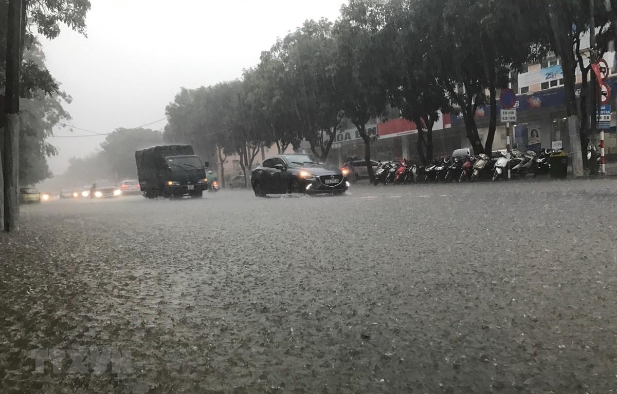 Nhiều tuyến đường ngập nước khiến phương tiện tham gia giao thông gặp nhiều khó khăn tại thành phố Vinh. (Ảnh: Bích Huệ/TTXVN)