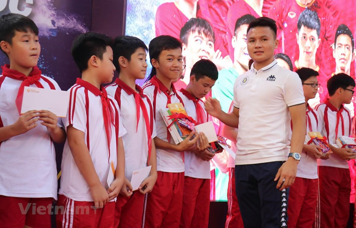 Quang Hải tặng sách cho các học sinh trường THCS Nam Trung Yên. (Ảnh: Vietnam+)