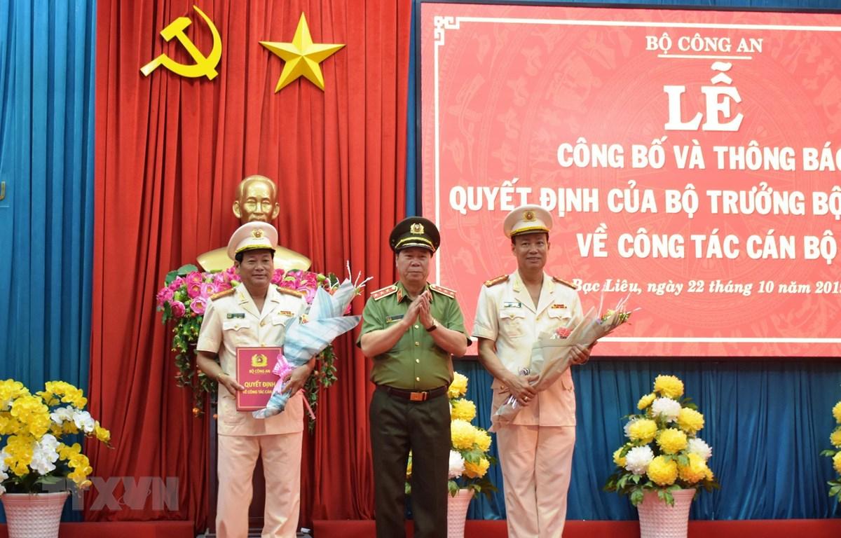 Thứ trưởng Bùi Văn Nam tặng hoa chúc mừng Đại tá Lê Tấn Tới và Đại tá Trần Phong. (Ảnh:TTXVN)
