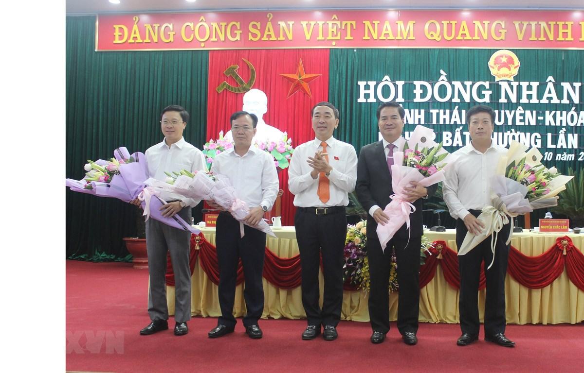 Bí thư Tỉnh ủy Thái Nguyên Trần Quốc Tỏ (người ở giữa) tặng hoa chúc mừng Phó Chủ tịch tỉnh và các Ủy viên UBND tỉnh mới được bầu tại kỳ họp. (Ảnh: Hoàng Nguyên/TTXVN)