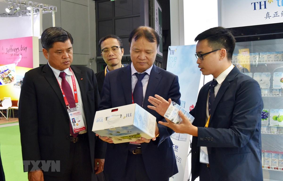 Thứ trưởng Nông nghiệp Trần Thanh Nam (trái) và Thứ truởng Công thương Đỗ Thắng Hải (giữa) tham quan gian hàng TH Truemilk. (Ảnh: Anh Tuấn/TTXVN)