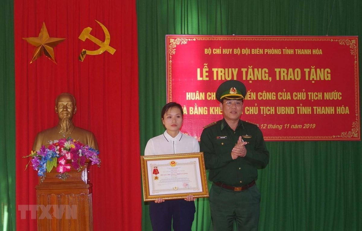 Vợ thiếu tá Vi Văn Nhất đón nhận Huân chương Chiến công hạng Nhất. (Ảnh: Trịnh Duy Hưng- TTXVN)