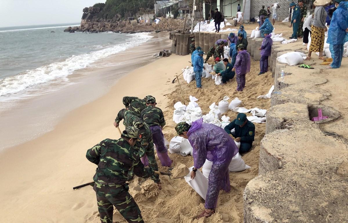 Lực lượng vũ trang tại tỉnh Bình Định xúc cát giúp người dân xã Nhơn Hải, TP Quy Nhơn gia cố nhà cửa chống bão số 6. (Ảnh: Nguyên Linh -TTXVN)