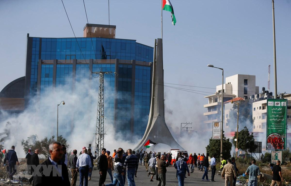 Người dân Palestine xung đột với các lực lượng an ninh Israel trong cuộc biểu tình tại thành phố Ramallah, Bờ Tây. (Ảnh: AFP/TTXVN)