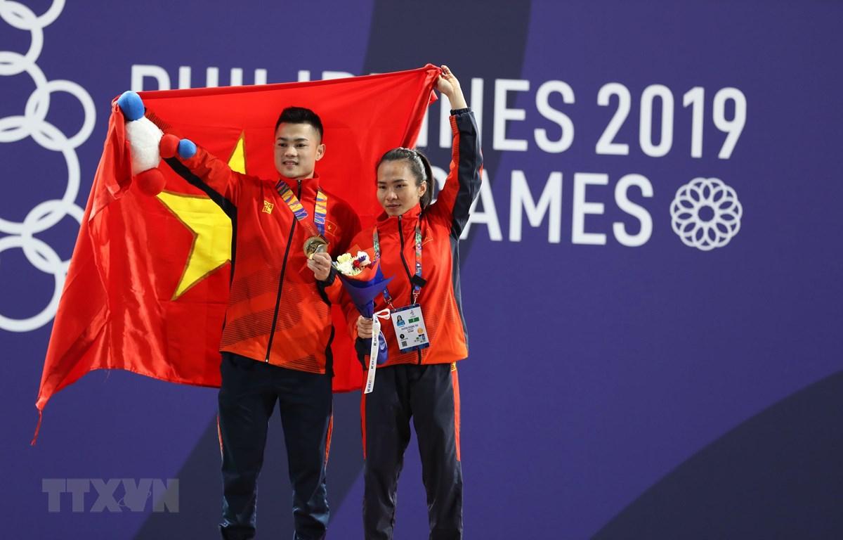 Lại Gia Thành (bên phải) và Vương Thị Huyền (cử tạ nữ) ăn mừng chiến thắng. (Ảnh: Hoàng Linh/TTXVN)