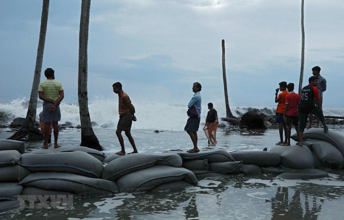 Người dân đặt bao cát ngăn các con sóng lớn do ảnh hưởng của bão Maha tại Chellanam, Ấn Độ. (Ảnh: AFP/TTXVN)