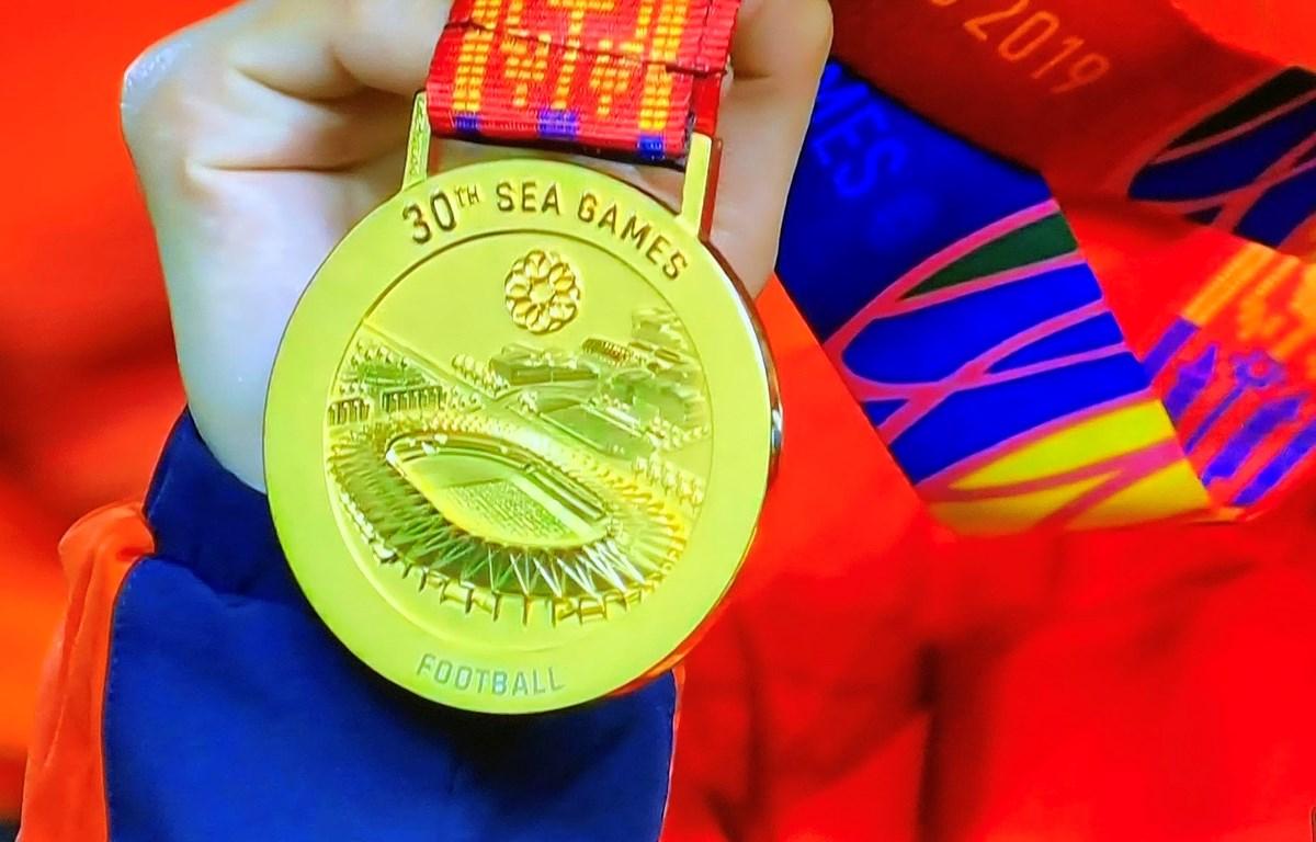 Các tuyển thủ nữ Việt Nam trò chuyện trên bục nhận huy chương vàng. (Ảnh: Hoàng Linh/TTXVN)