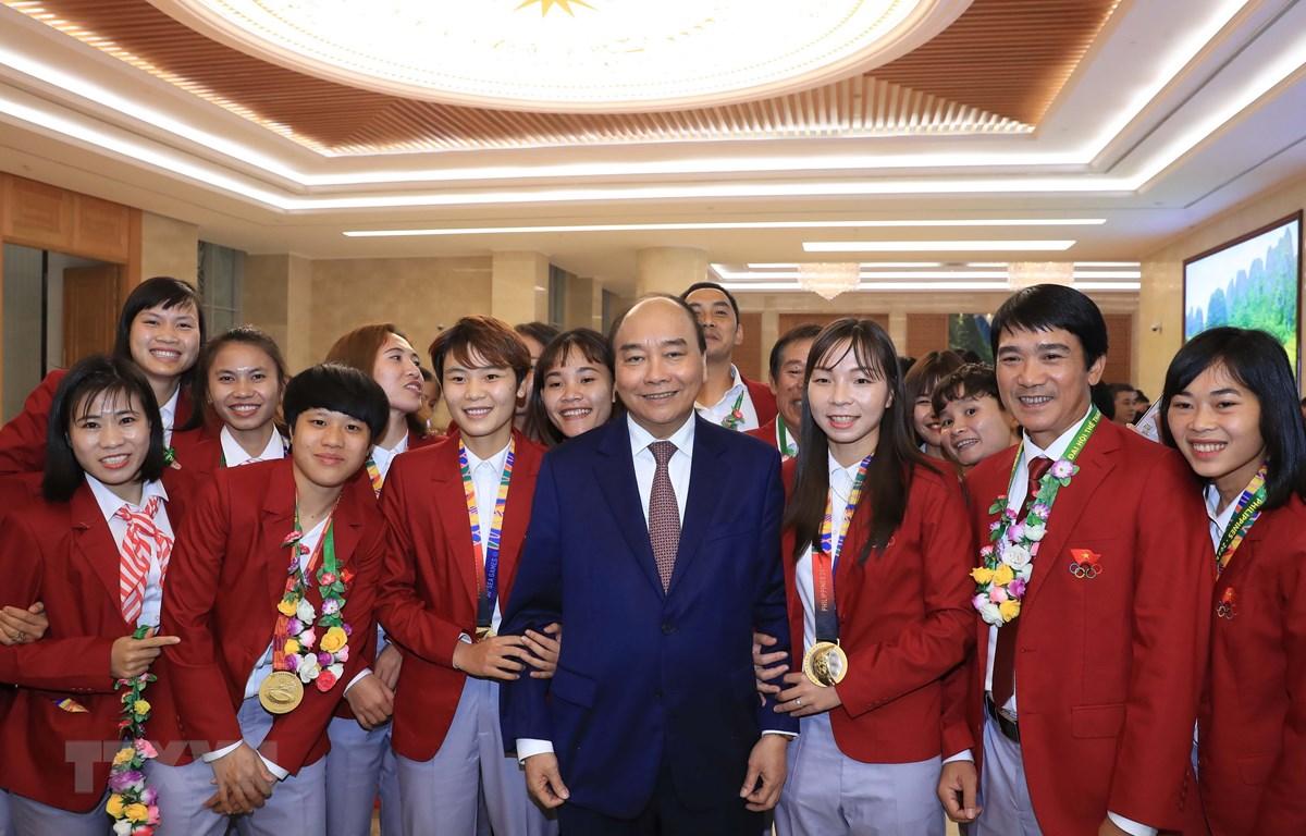 Thủ tướng Nguyễn Xuân Phúc chụp ảnh chung với các tuyển thủ bóng đá nữ quốc gia. (Ảnh: Thống Nhất/TTXVN)