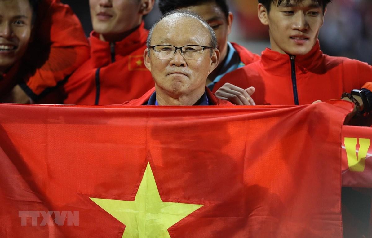 HLV Park Hang Seo với quốc kỳ Việt Nam. (Ảnh: Hoàng Linh/TTXVN)