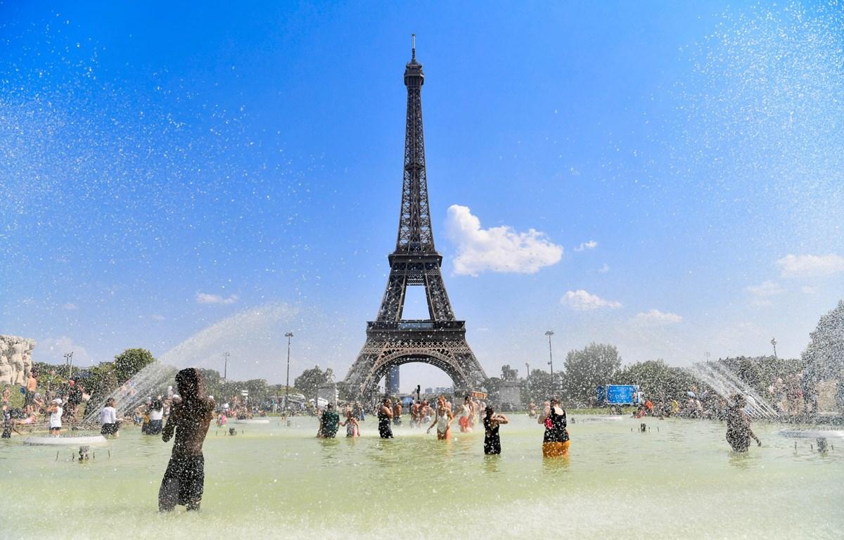 Người dân tránh nóng bên vòi phun nước tại Paris, Pháp. (Ảnh: THX/TTXVN)