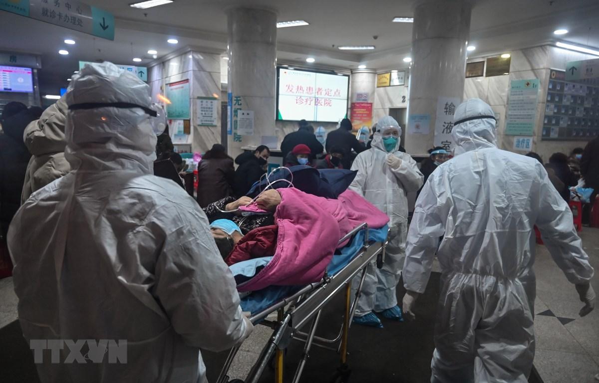 Nhân viên y tế chuyển bệnh nhân nhiễm virus corona mới gây bệnh viêm phổi tới bệnh viện ở Vũ Hán, tỉnh Hồ Bắc, Trung Quốc. (Ảnh: AFP/TTXVN)