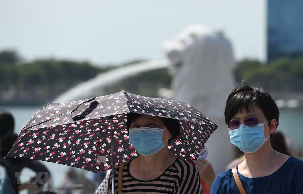 Người dân đeo khẩu trang để phòng tránh lây nhiễm virus corona tại Singapore. (Ảnh: AFP/TTXVN)