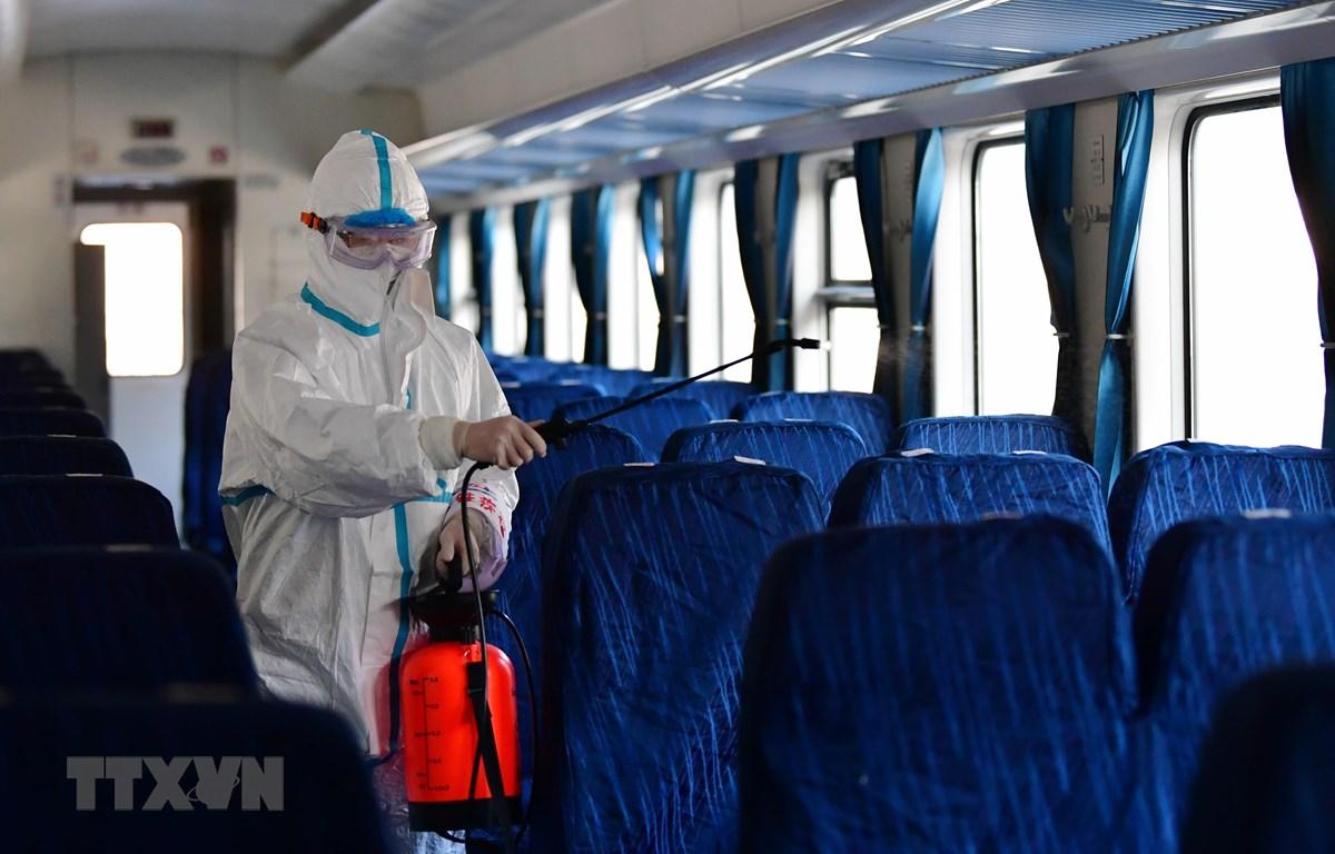 Lực lượng chức năng tiến hành khử trùng các thiết bị trên một đoàn tàu ở nhà ga đường sắt tại Lan Châu, tỉnh Cam Túc, Trung Quốc. (Ảnh: THX/TTXVN)
