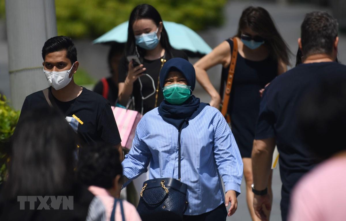 Người dân đeo khẩu trang để phòng tránh lây nhiễm virus corona chủng mới tại Singapore ngày 4/2. (Ảnh: AFP/ TTXVN)