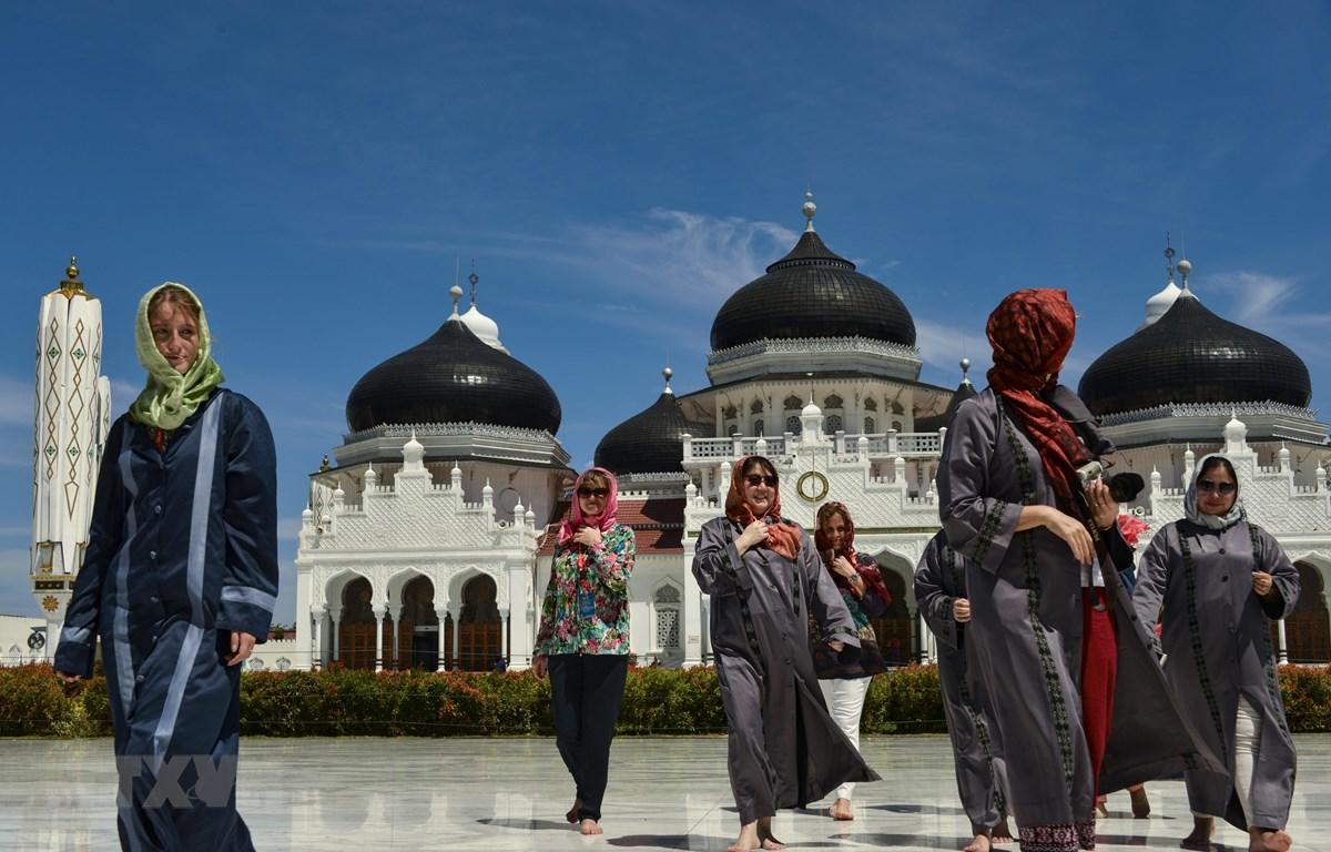 Khách du lịch nước ngoài thăm nhà thờ Hồi giáo Baiturrahman ở Banda Aceh, Indonesia. (Ảnh: AFP/TTXVN)