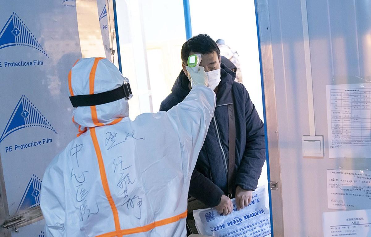 Nhân viên y tế kiểm tra thân nhiệt cho bệnh nhân nhiễm nCoV tại một bệnh viện dã chiến ở Vũ Hán, Trung Quốc. (Ảnh: THX/TTXVN)