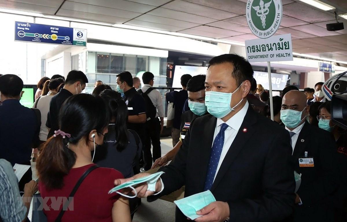 Bộ trưởng Y tế Thái Lan Anutin Charnvirakul (phải) phát khẩu trang cho hành khách tại một nhà ga ở Bangkok. (Ảnh: AFP/TTXVN)