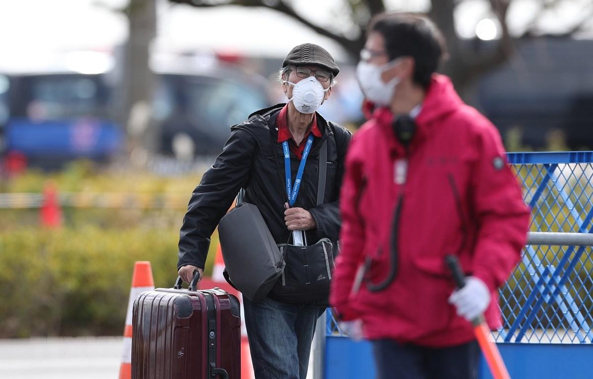 Hành khách rời khỏi du thuyền Diamond Princess tại Yokohama, Nhật Bản, ngày 19/2. (Ảnh: THX/TTXVN)