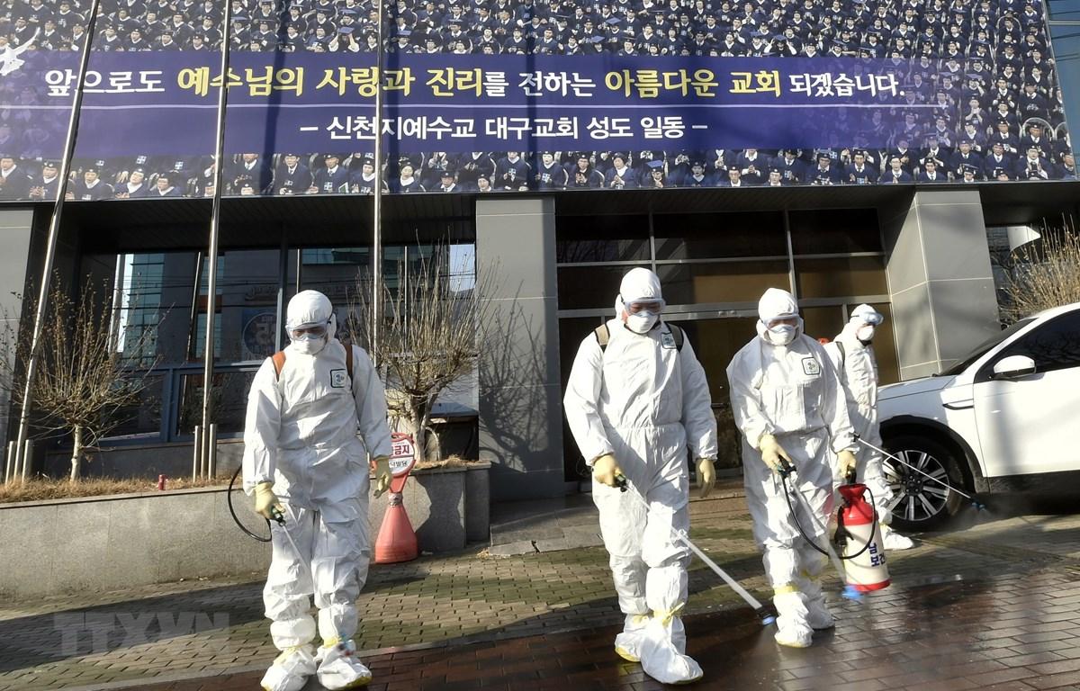 Nhân viên y tế phun thuốc khử chùng ngăn chặn sự lây lan của dịch bệnh COVID-19 tại Daegu, Hàn Quốc ngày 19/2. (Ảnh: AFP/TTXVN)
