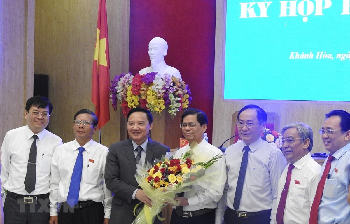 Lãnh đạo tỉnh Khánh Hòa tặng hoa, chúc mừng ông Nguyễn Tấn Tuân (giữa) sau khi được bầu giữ chức vụ Chủ tịch UBND tỉnh. (Ảnh: Tiên Minh/TTXVN)