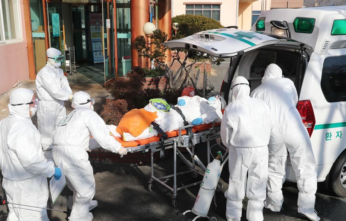 Nhân viên y tế chuyển bệnh nhân nhiễm COVID-19 lên xe cứu thương tại thành phố Daegu, Hàn Quốc. (Ảnh: AFP/TTXVN)
