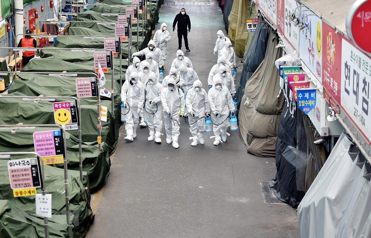 Trong ảnh: Nhân viên phun thuốc khử trùng tại một khu chợ ở Daegu, Hàn Quốc, nhằm ngăn chặn sự lây lan của COVID-19. (Ảnh: THX/TTXVN)