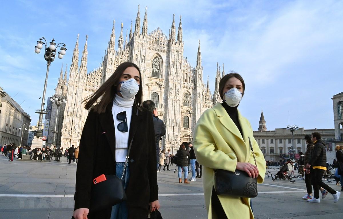 Người dân đeo khẩu trang phòng dịch viêm đường hô hấp cấp COVID-19 tại quảng trường del Duomo ở Milan, Italy ngày 23/2. (Ảnh: AFP/TTXVN)