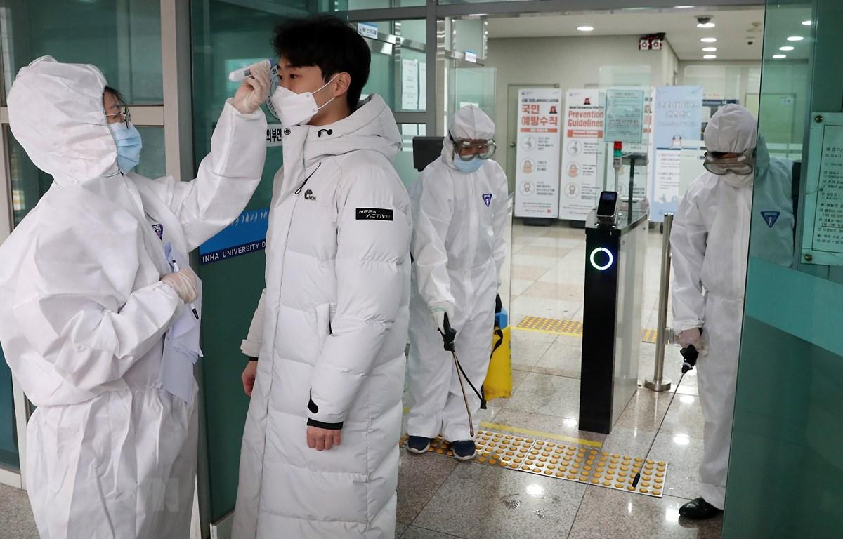 Nhân viên y tế kiểm tra thân nhiệt của sinh viên tại trường đại học Inha ở Incheon, Hàn Quốc. (Ảnh: THX/TTXVN)