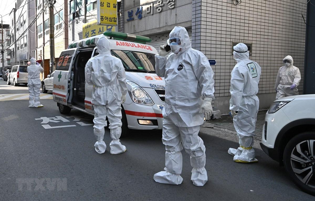 Nhân viên y tế Hàn Quốc làm nhiệm vụ tại một khu dân cư ở thành phố Daegu, nơi phát hiện các trường hợp có triệu trứng nhiễm virus SARS-CoV-2, ngày 27/2. (Ảnh: AFP/TTXVN)