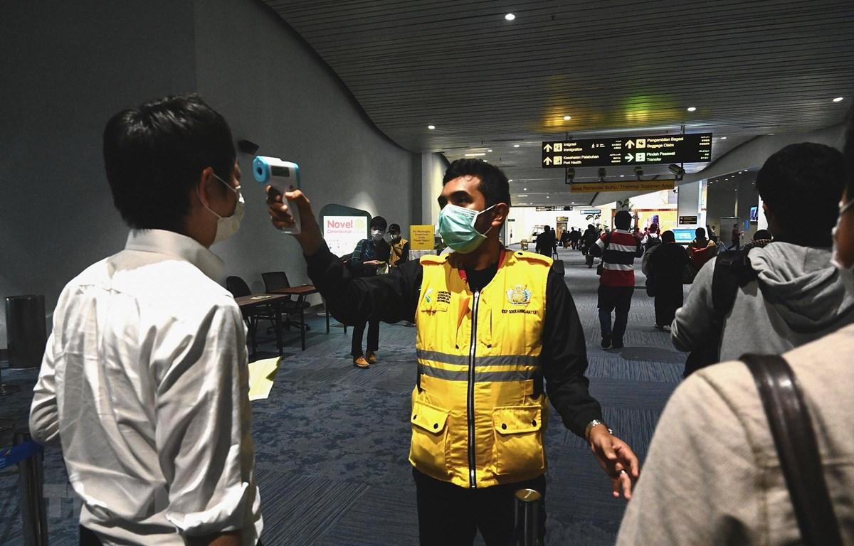 Nhân viên y tế Indonesia kiểm tra thân nhiệt hành khách tại sân bay quốc tế Jakarta nhằm ngăn chặn sự lây lan của dịch bệnh COVID-19. (Ảnh: AFP/TTXVN)