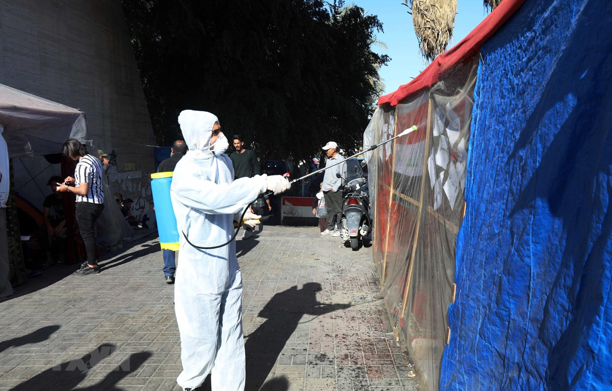 Nhân viên y tế phun thuốc khử trùng nhằm ngăn chặn sự lây lan của dịch COVID-19 tại Baghdad, Iraq. (Ảnh: THX/TTXVN)