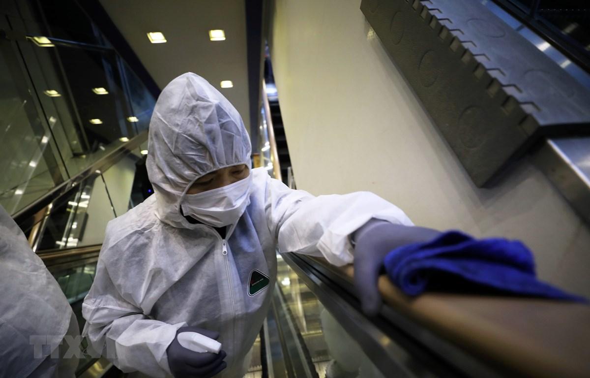Nhân viên khử trùng tay nắm cầu thang tại một trung tâm thương mại ở Seoul, Hàn Quốc nhằm ngăn chặn sự lây lan của COVID-19. (Ảnh: THX/TTXVN)
