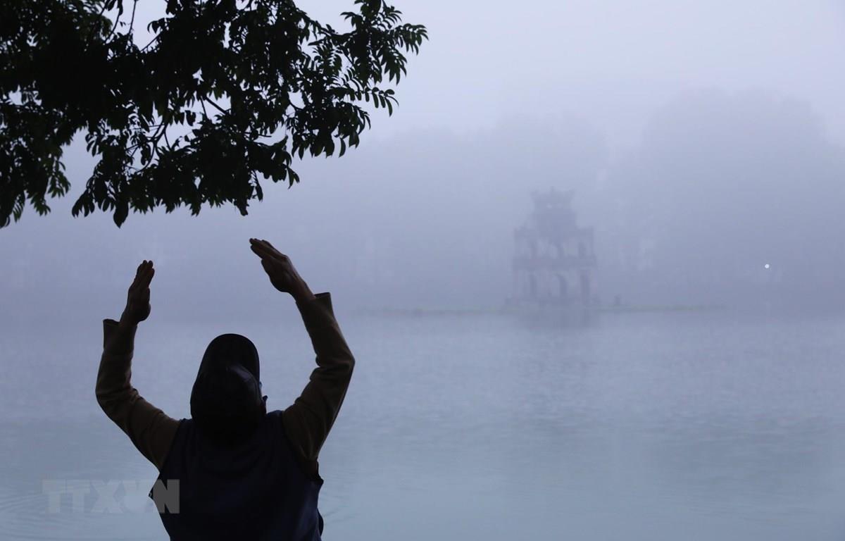 Một người đàn ông tập thể dục bên hồ Hoàn Kiếm, Hà Nội trong sương sớm. (Ảnh: Lâm Khánh/TTXVN)