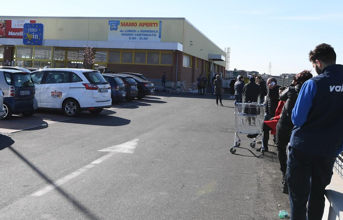 Người dân xếp hàng bên ngoài một siêu thị ở Rome, Italy. (Ảnh: THX/TTXVN)