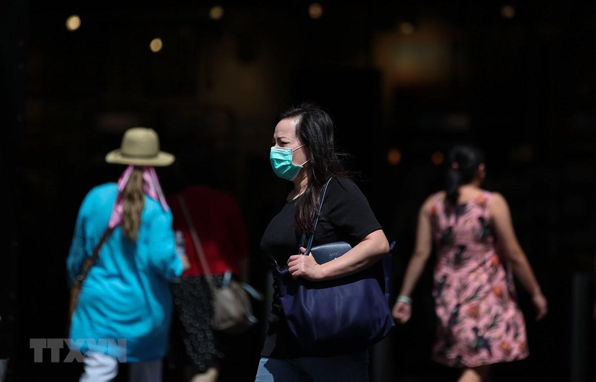 Người dân đeo khẩu trang để phòng tránh lây nhiễm COVID-19 tại Sydney, Australia. (Ảnh: THX/TTXVN)