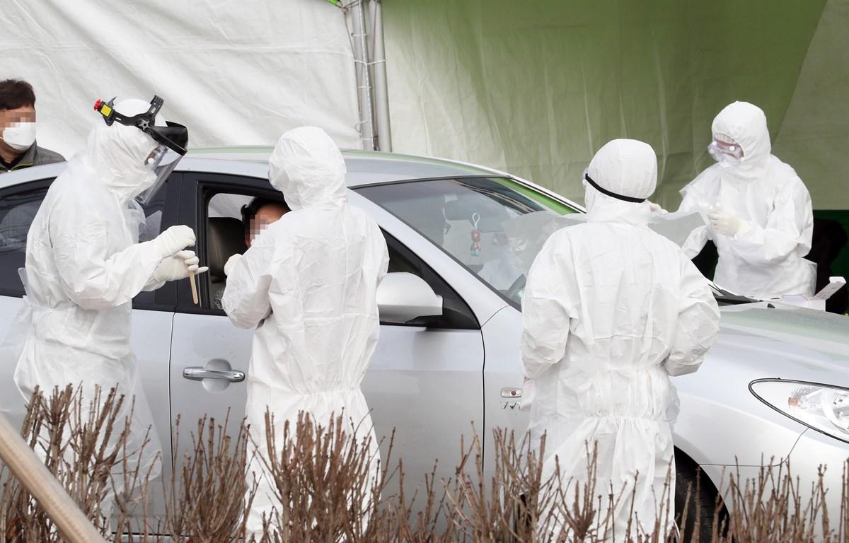 Nhân viên y tế lấy mẫu xét nghiệm của bệnh nhân nghi nhiễm COVID-19 tại tòa nhà ở Sejong, Hàn Quốc. (Ảnh: Yonhap/TTXVN)