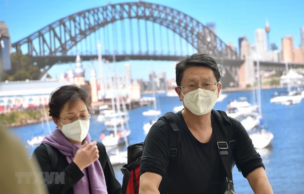 Hành khách đeo khẩu trang phòng lây nhiễm COVID-19 tại sân bay ở Sydney, Australia. (Ảnh: AFP/TTXVN)