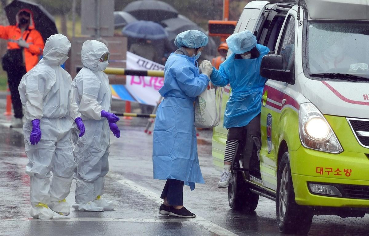 Nhân viên y tế hỗ trợ bệnh nhân mắc COVID-19 tại một bệnh viện ở thành phố Daegu, Hàn Quốc. (Ảnh: THX/TTXVN)