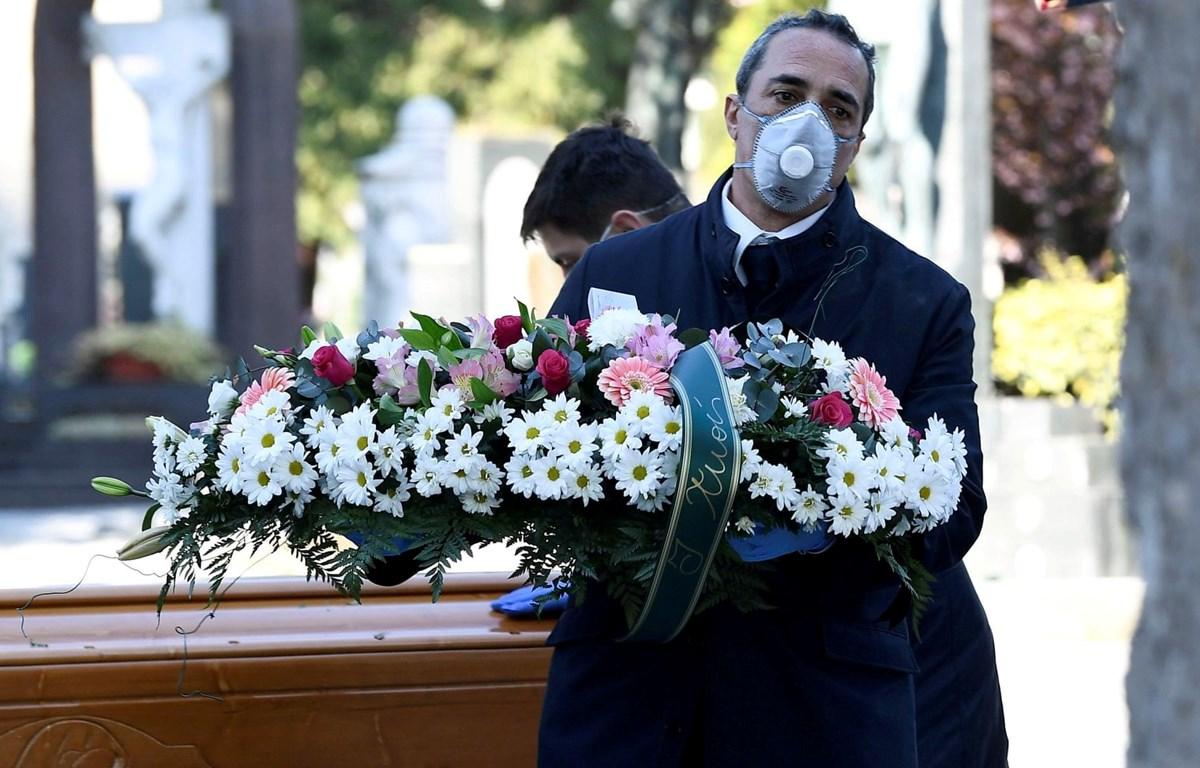 Nhân viên nhà tang lễ vận chuyển quan tài của một nạn nhân nhiễm virus SARS-CoV-2 vào một nghĩa trang ở Bergamo. (Ảnh: Reuters)
