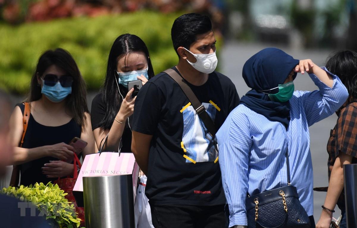 Người dân đeo khẩu trang phòng dịch COVID-2 tại Singapore. (Ảnh: AFP/TTXVN)