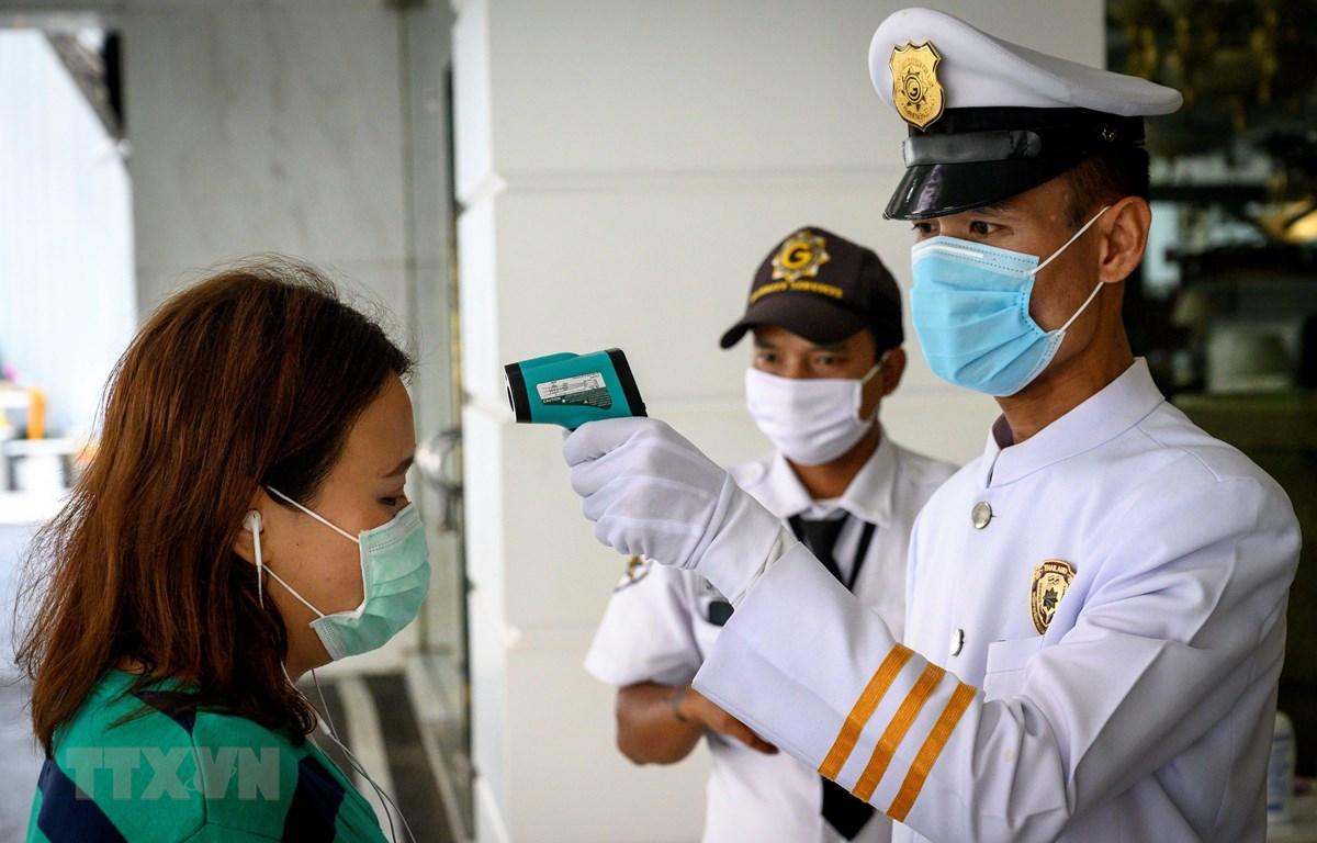 Nhân viên an ninh kiểm tra thân nhiệt người dân nhằm ngăn chặn sự lây lan của dịch COVID-19 tại Bangkok. (Ảnh: AFP/TTXVN)